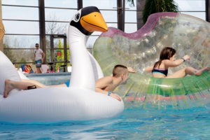 medencében felfújható játékokkal játszó gyerekek