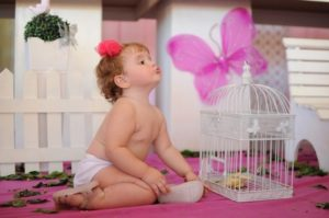 kislány ül egy rózsaszín takarón egy madárkalitka előtt
